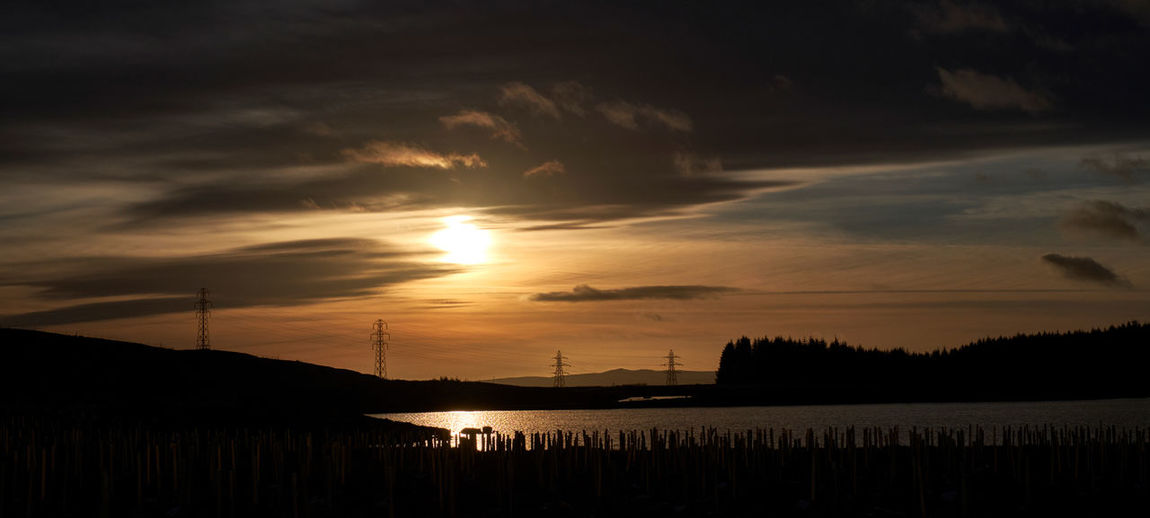 Highlands Sunset Pylons And Power Lines Powerlines Electricity  Lake Lake View Powerline Sky Cloud - Sky Silhouette Beauty In Nature Scenics - Nature Outdoors Sun Orange Color Non-urban Scene Man Shaping Nature