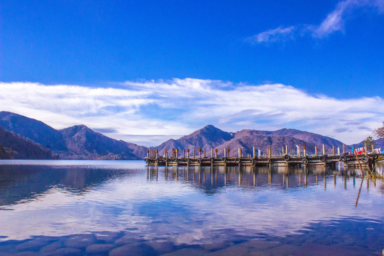 Calm lake with mountain range against blue sky