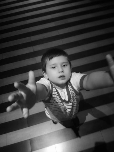 High angle portrait of boy gesturing while standing on striped floor