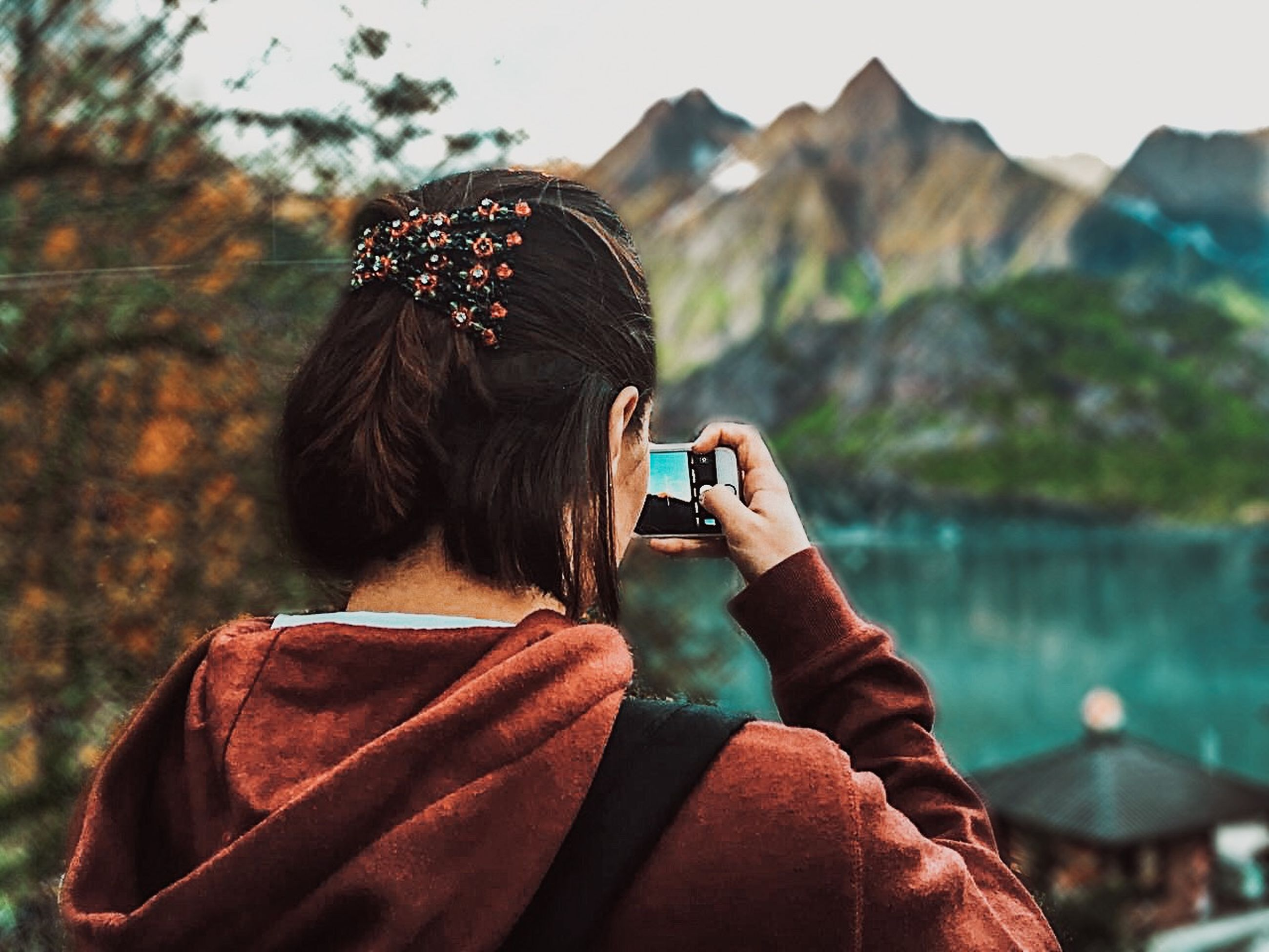 real people, activity, one person, lifestyles, leisure activity, photography themes, photographing, technology, rear view, wireless technology, headshot, holding, smart phone, mobile phone, portrait, water, portable information device, nature, women, outdoors, hairstyle