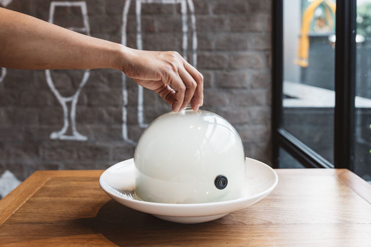 Male hand lifts to up glass cloche from a plate with hot food at restaurant - Smoked food time! Close Up. Human Hand Hand Real People One Person Human Body Part Holding Table Indoors  Focus On Foreground White Color Lifestyles Men Day Adult Piggy Bank Close-up Unrecognizable Person Body Part Women Finger Human Limb