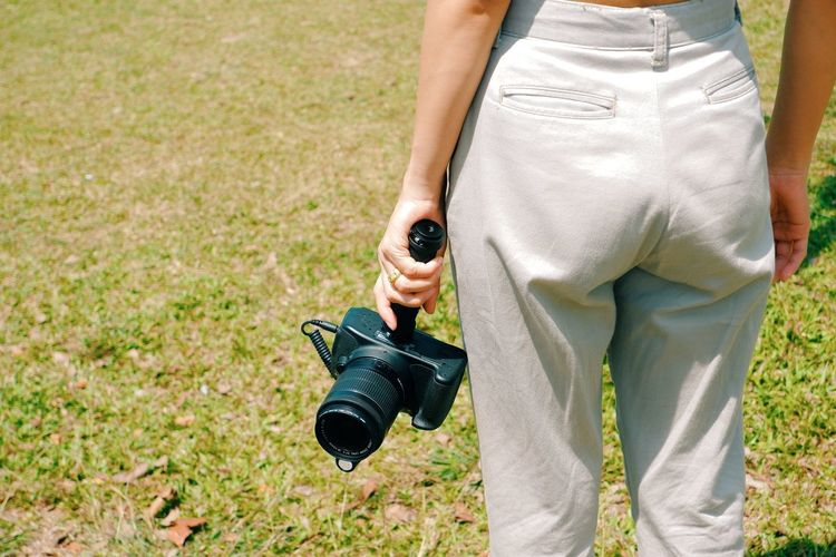 Midsection of man holding camera while standing on grass