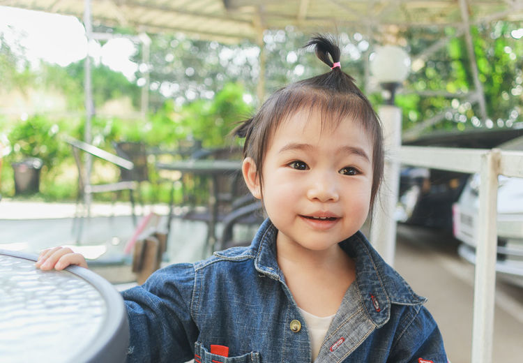 Close-up of cute baby girl sitting on chair outdoors