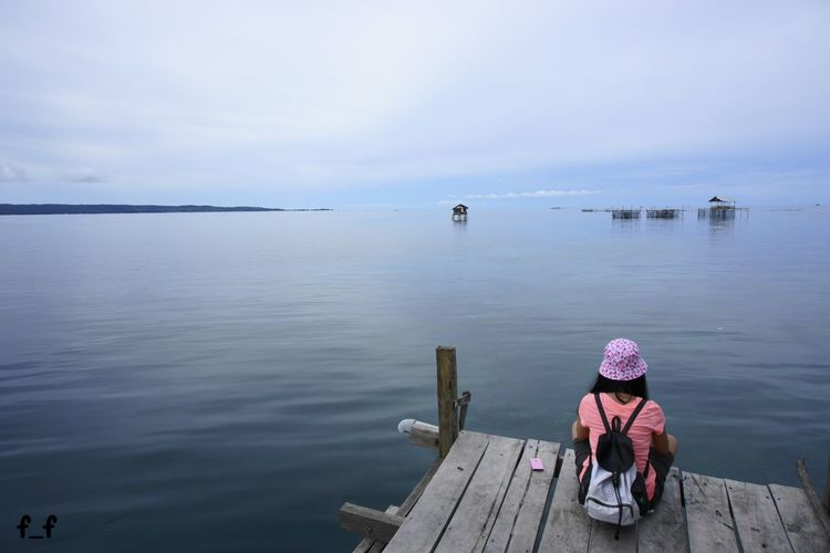 Rear View Of Woman Sitting On Pier