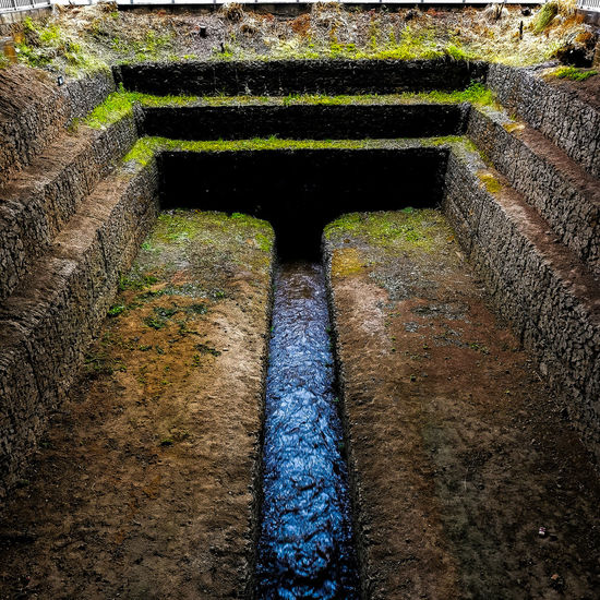 High angle view of water flowing through old wall
