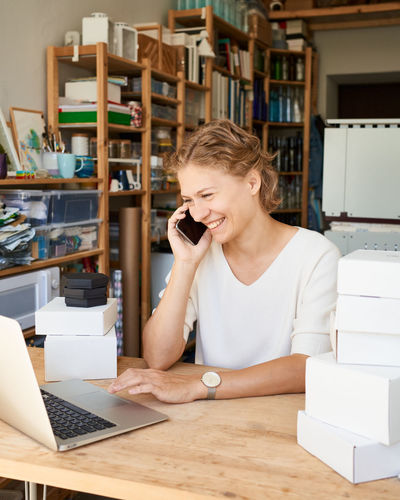 Smiling woman woman using laptop while talking on phone at office