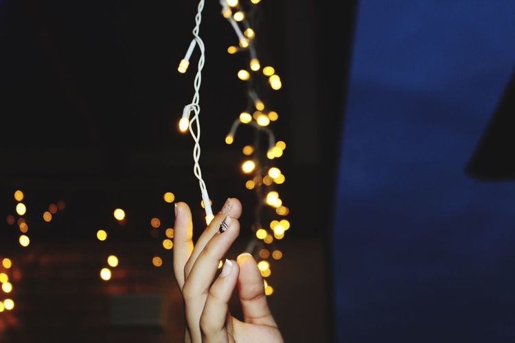 Close-up of hands holding string lights at night