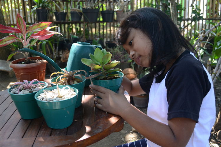 Side view of girl holding potted plant