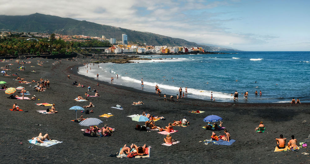 Puerto de la cruz, Tenerife, Canary islands. People sunbathing and relaxation in Playa Jardin. One of the best black sand beaches in Tenerife Canary Islands Puerto De La Cruz SPAIN Beach Black Sand Beach Crowd Day Enjoyment Large Group Of People Nature Outdoors People Real People Sand Sea Sky Tenerife Tenerife Island Togetherness Volcanic  Water