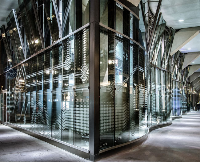 Illuminated modern building seen through glass window at night