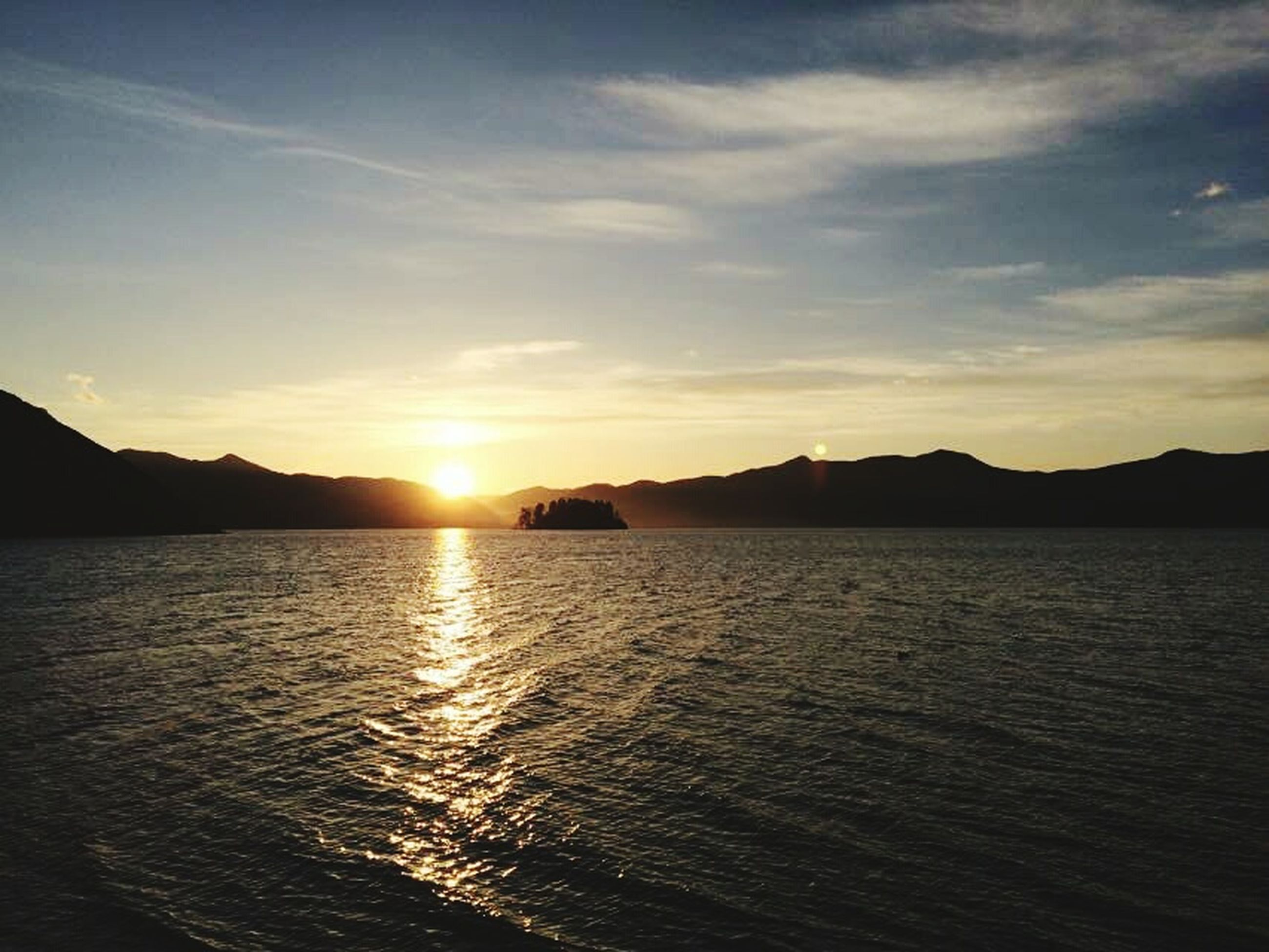 water, mountain, scenics, sunset, tranquil scene, silhouette, tranquility, sun, beauty in nature, sea, reflection, mountain range, idyllic, sky, nature, cloud - sky, non-urban scene, back lit, tourism, majestic, vacations, sunbeam, no people, waterfront, seascape, vibrant color