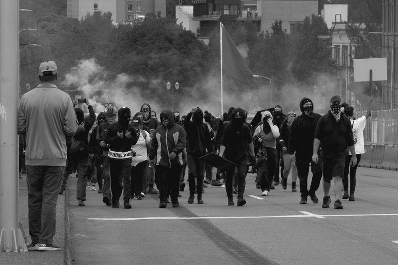Protestors walking on road in city