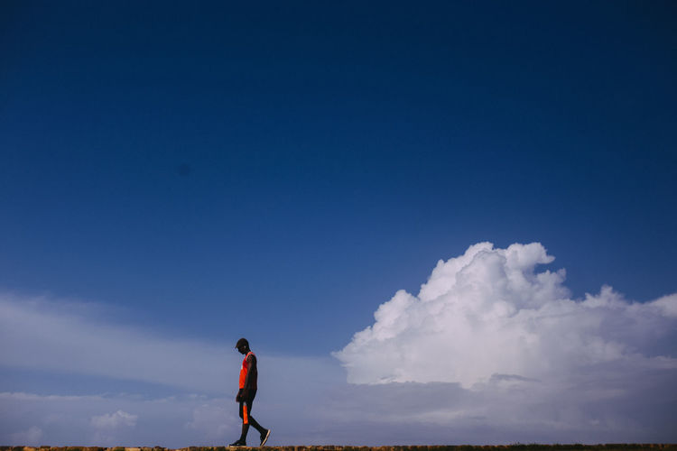 Side view of man walking against blue sky