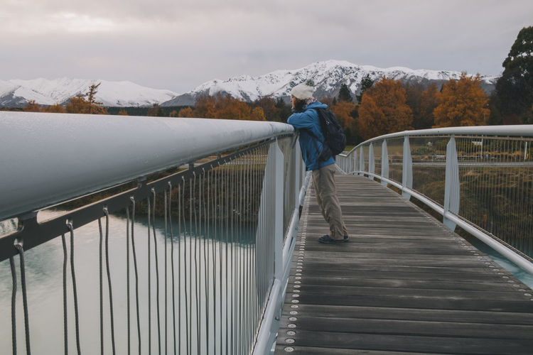 Rear view of person standing on footbridge