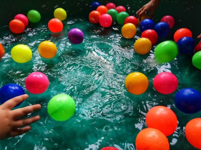 Cropped hands of children holding balls in wading pool