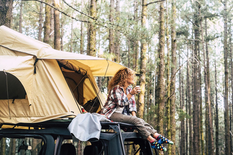 Low angle view of woman sitting on motor van in forest