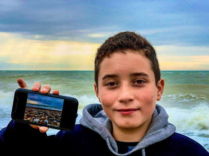 Portrait of boy showing photograph on mobile phone at beach against sky