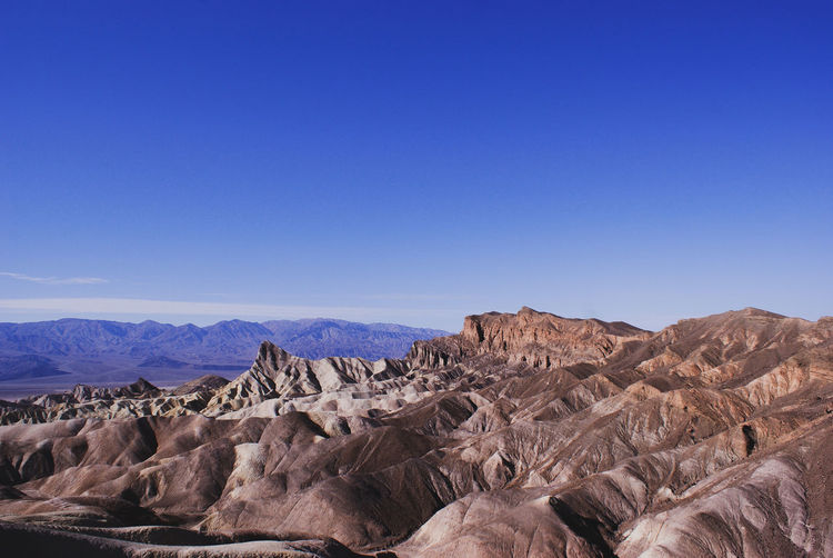 Scenic view of dramatic landscape against clear blue sky