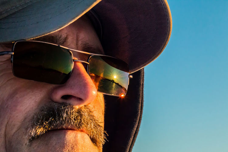 Close-up of mature man wearing sunglasses with reflection during sunset