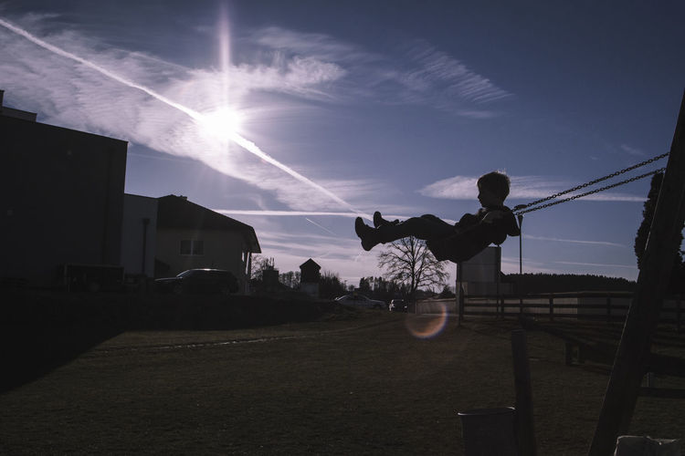 Silhouette boy swinging against sky at playground during sunny day