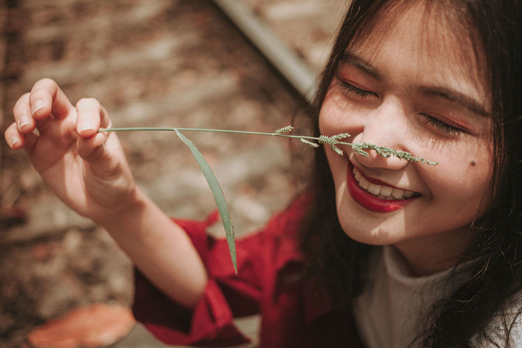 Close-up of smiling young woman holding plant on nose