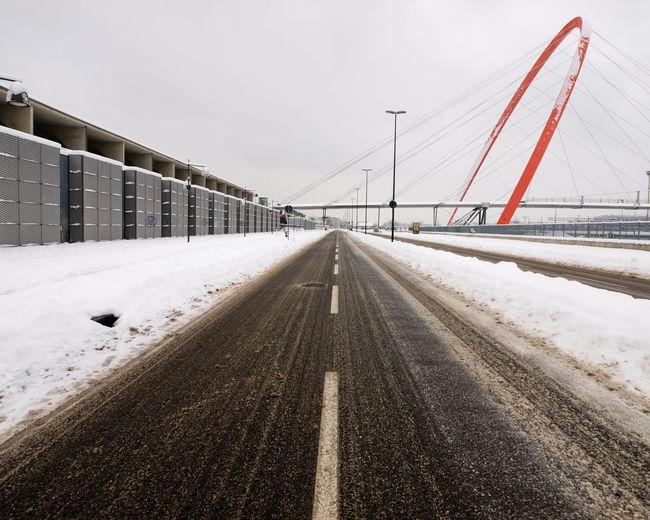 Road leading towards bridge against sky during winter