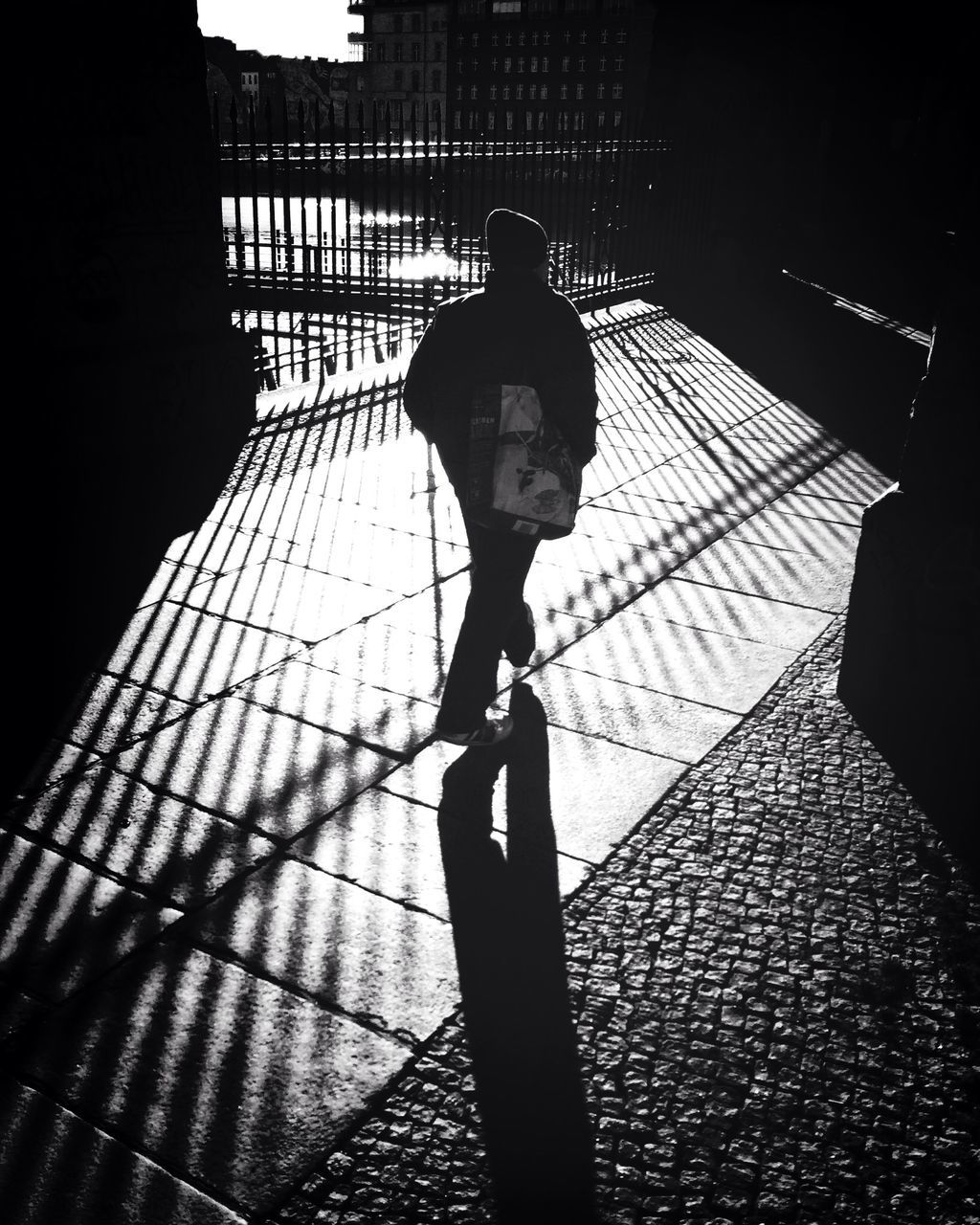 shadow, sunlight, full length, one person, real people, silhouette, lifestyles, walking, outdoors, day, city, men, standing, architecture, building exterior, one man only, people