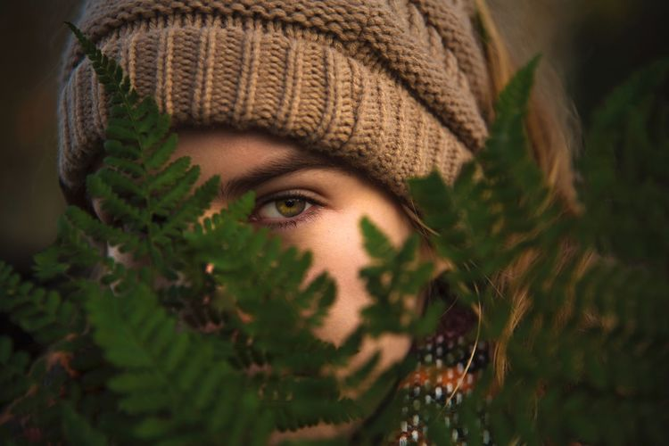Close-up portrait of teenage girl wearing knit hat by plants