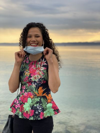 Beautiful young woman drinking water from beach