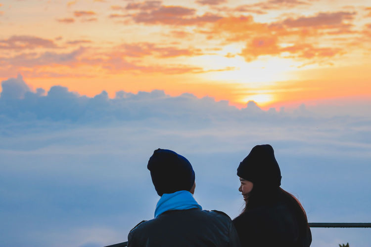 Young couple looking at view while standing on observation point against sky during sunset