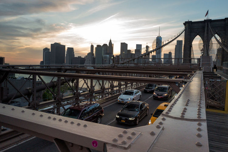 Vehicles moving under brooklyn bridge road over east river