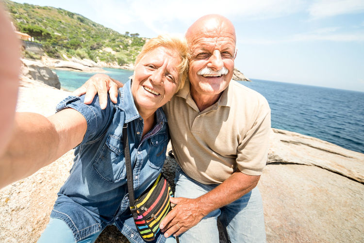 Portrait of smiling couple sitting on beach against sky during sunny day