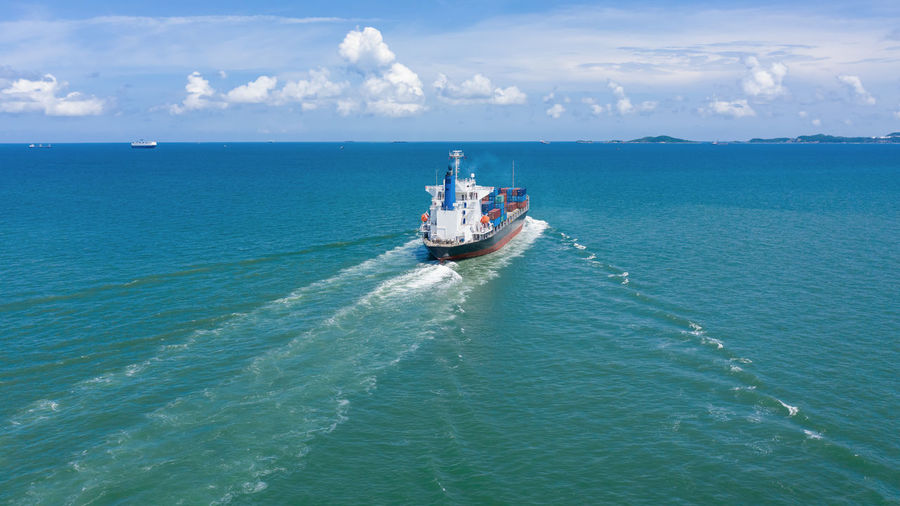 Shipping container sailing in sea against sky