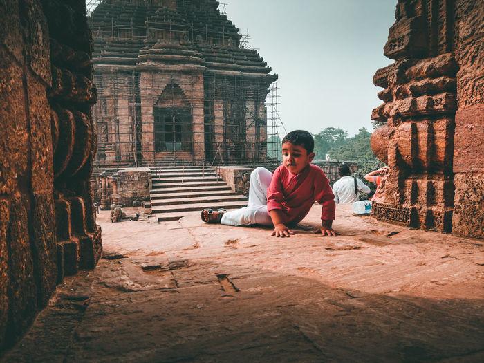 Full length of man sitting outside temple