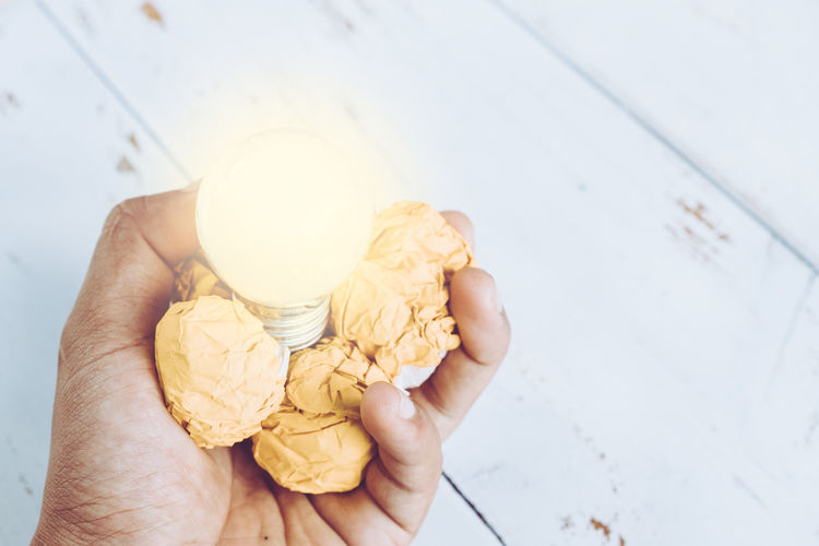Close-up of hand holding illuminated light bulb and crumpled paper