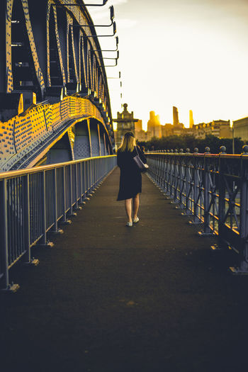 Woman walking on footbridge