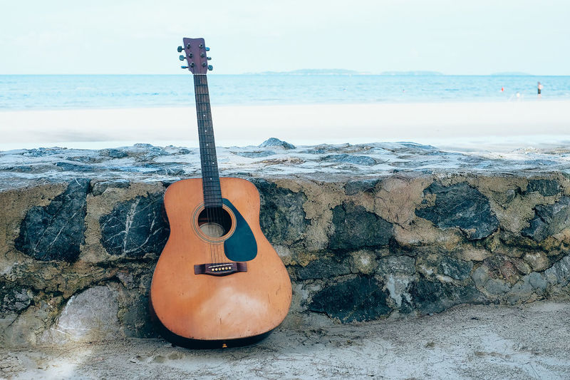 Summer traveling with guitar , beach background. Summer and Travel Concept. Beach Guitar Summer Travel Sea Sand Music Nature Sun Re String Instrument Musical Instrument Musical Equipment Water Acoustic Guitar Arts Culture And Entertainment Musical Instrument String String Land Solid Horizon Rock No People Horizon Over Water Rock - Object Day Outdoors