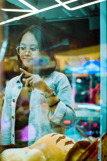 Portrait of young woman in store window