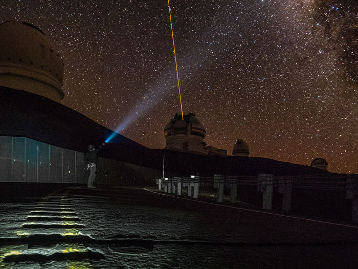 Low angle view of illuminated building against star field at night