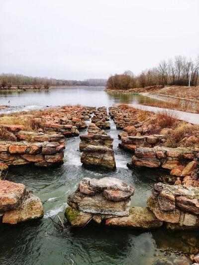 Panoramic shot of rocks in river against sky