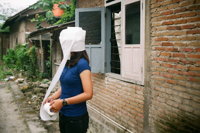 Woman with head wrapped in toilet paper