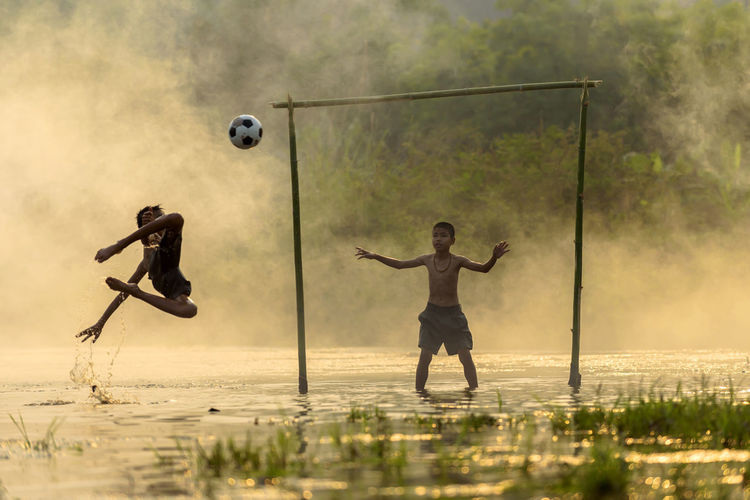 Boys playing soccer in swamp