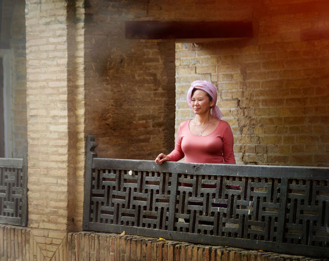 Woman standing by railing against brick wall