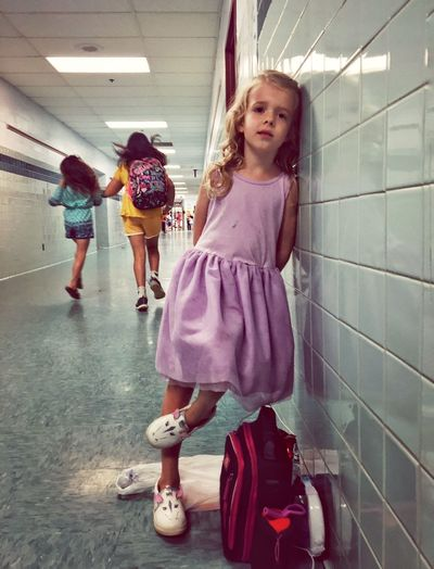 Portrait Of Cute Girl With Backpack Leaning On Tiled Wall In Corridor