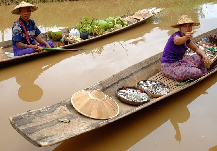 Vendors sitting on boats in river at floating market