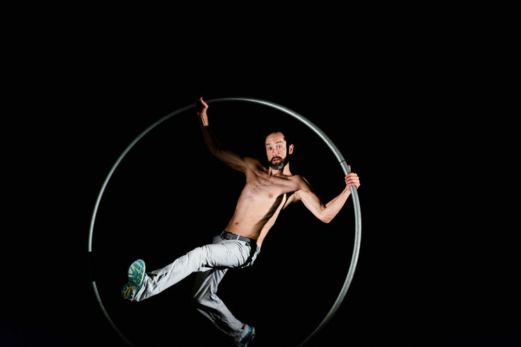 Circus Adult Arms Raised Arts Culture And Entertainment Black Background Circle Copy Space Dark Front View Full Length Holding Human Arm Indoors  Lifestyles Men Motion One Person Performance Plastic Hoop Shirtless Skill  Studio Shot Young Adult