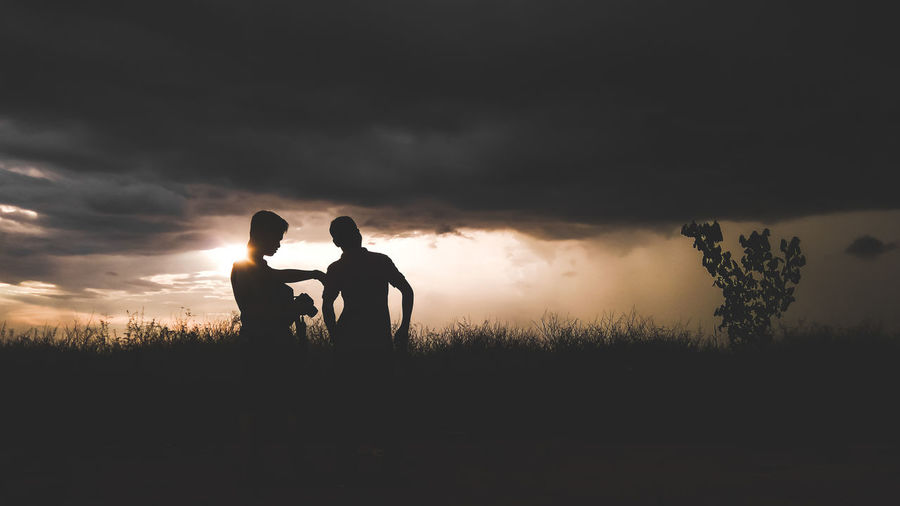 Silhouette father with son on grassy field against cloudy sky