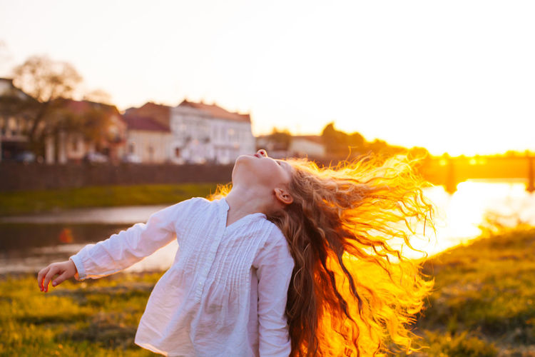 Woman with arms outstretched standing against sky during sunset