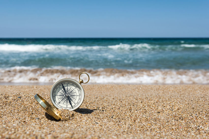 Compass on the golden sand by the sea Choice Decisions Golden Storytelling Backgrounds Beach Brass Compass Concept Conceptual Dilemma Direction Discovery Exploration Guidance Inspiration Metal Outdoors Sand Sea Searching Seeking Wave Where Which Way?