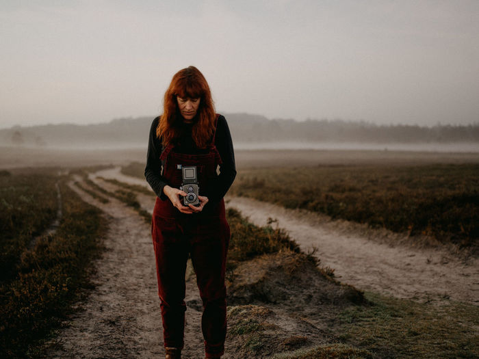 Woman holding camera standing on field